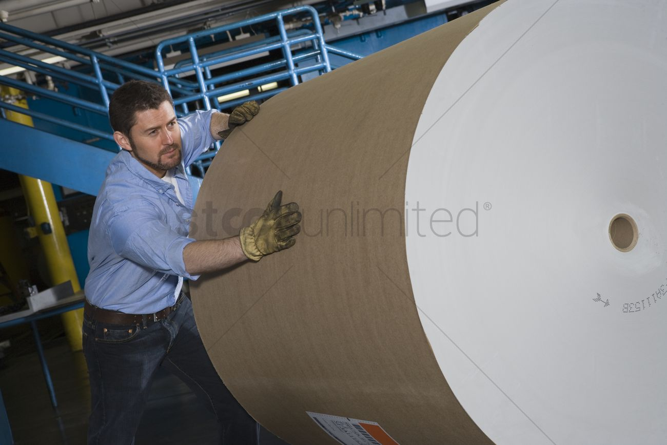 man-pushing-huge-roll-of-paper-in-newspa