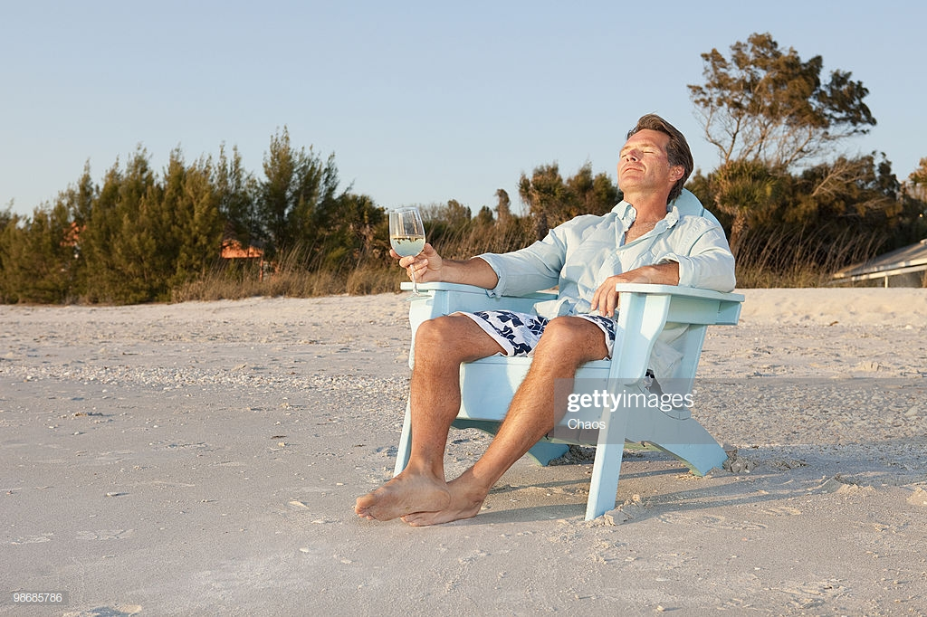 man-relaxing-in-the-sunset-and-drinking-