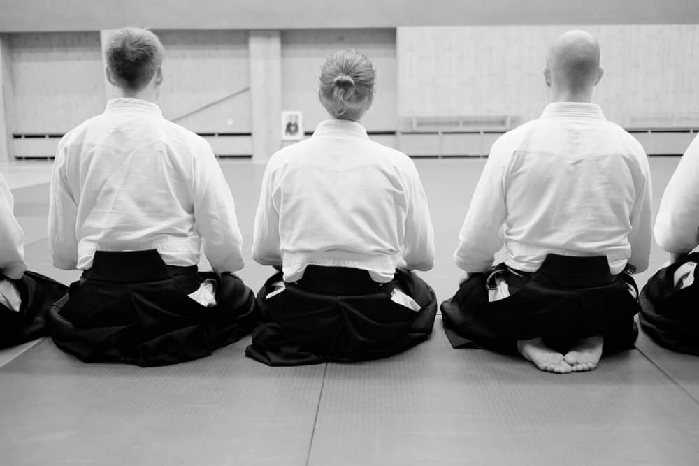 Aikido-training-participants-sit-on-a-ma